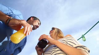 Funny drunk couple looking down at camera, toasting and drinking cocktails