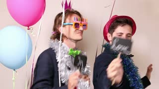 Funny male friends dancing with a sign in love in photo booth
