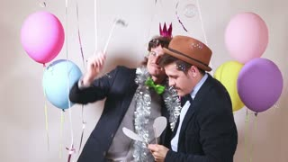 Funny male friends dancing with props