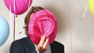 Funny man with pink hat dancing in photo booth