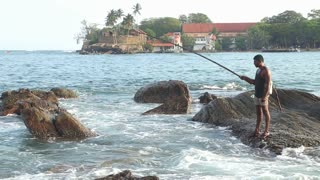 GALLE, SRI LANKA - MARCH 2014: Local fisherman fishing from a rock in Galle. These people find it more difficult to make a living due to over-fishing.