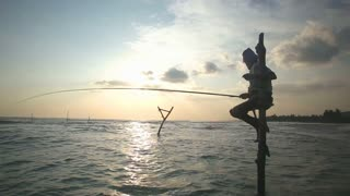 GALLE, SRI LANKA - MARCH 2014: Silhouette of elderly fisherman on a fishing pole at sunset. Stilt fishing is a tradition that only 500 fishing families of Galle practice.