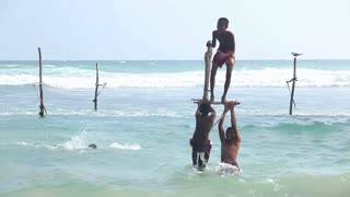 GALLE, SRI LANKA - MARCH 2014: Young boys playing on a fishing pole in the ocean. Stilt fishing is a tradition that only about 500 fishing families in the district of Galle practice.