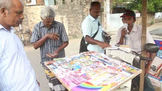 GALLE, SRI LANKA - MARCH 7, 2014: People buying lottery tickets on street stand.