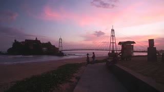 GALLE, SRI LANKA - MARCH 7, 2014: Small island connected with bridge at sunset. Galle  is a popular destination for children, vendors, teenagers, lovers.