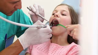 Girl showing thumbs up at dentist
