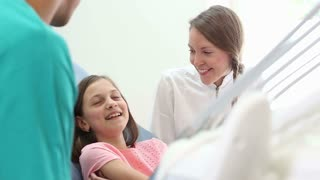 Girl sitting in dental chair, talking with female dentist and male surgeon