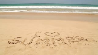 Girl walking in front of words I love summer written in sand on beach