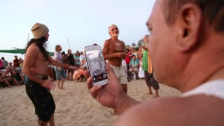 GOA, INDIA - 19 JANUARY 2015: Man filming on mobile phone people dancing on the beach.
