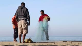 GOA, INDIA - 20 JANUARY 2015: Fishermen carrying fishing net on shore in Goa.