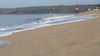 GOA, INDIA - 20 JANUARY 2015: Man running at sandy beach in Goa.