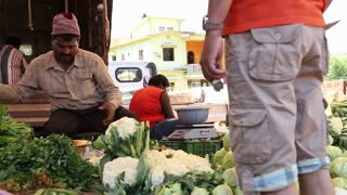 GOA, INDIA - 20 JANUARY 2015: Man selling vegetables at market stand in Goa.