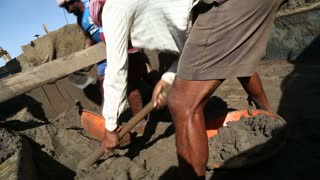 GOA, INDIA - 20 JANUARY 2015: Men digging sand with wide hoe.