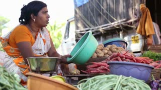 GOA, INDIA - 20 JANUARY 2015: Woman at market stand with vegetable in Goa.