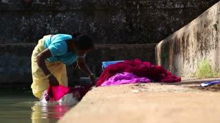 GOA, INDIA - 20 JANUARY 2015: Woman washing clothes in street washing pool in Goa.