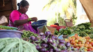 GOA, INDIA - 20 JANUARY 2015: Woman weighing vegetables at market stand in Goa.