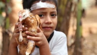 GOA, INDIA - 21 JANUARY 2015: Child holding young chicken.