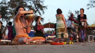 GOA, INDIA - 21 JANUARY 2015: Man doing a religious ritual at sandy beach in Goa while people passing.