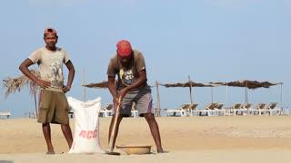 GOA, INDIA - 21 JANUARY 2015: Men collecting sand at sandy beach in Goa.