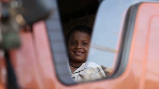 GOA, INDIA - 21 JANUARY 2015: Portrait of Indian boy sitting on the front seat of a truck.