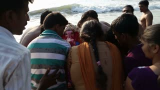 GOA, INDIA - 23 JANUARY 2015: Group of people carrying religious statue to water at beach in Goa.