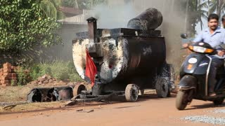 GOA, INDIA - 23 JANUARY 2015: Vehicles passing by smoky machinery on the road.