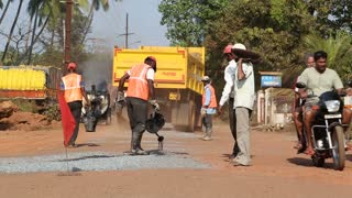 GOA, INDIA - 23 JANUARY 2015: Worker pouring water on pebble thrown on the road of construction site.