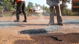 GOA, INDIA - 23 JANUARY 2015: Worker throwing pebble at the road's construction site.