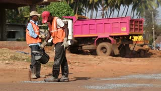 GOA, INDIA - 23 JANUARY 2015: Workers pouring water at the road's construction site.