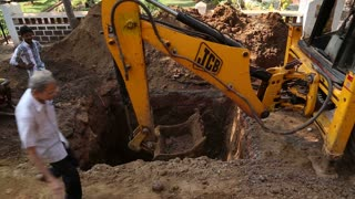 GOA, INDIA - 25 JANUARY 2015: Dredge digging soil at construction site, with man passing.