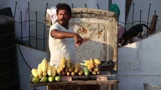 GOA, INDIA - 25 JANUARY 2015: Indian man roasting corn at the street stand in Goa.