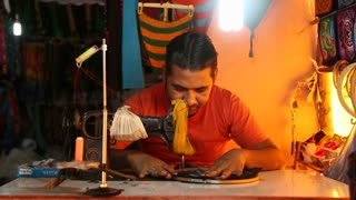GOA, INDIA - 25 JANUARY 2015: Indian man sewing using sewing machine in workshop.