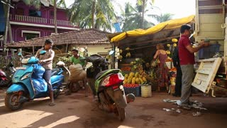 GOA, INDIA - 25 JANUARY 2015: Indian men preparing to ride motorbikes in front of shop in Goa.