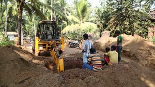 GOA, INDIA - 25 JANUARY 2015: Workers at construction site watching dredge digging soil.