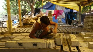 GOA, INDIA - 26 JANUARY 2015: Indian boy glazing cement blocks in a workshop.