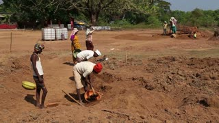 GOA, INDIA - 26 JANUARY 2015: Men and women working at the field working site digging soil.