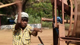 GOA, INDIA - 26 JANUARY 2015: Portrait of boy moving wheel of the soil processing machine.