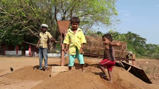 GOA, INDIA - 26 JANUARY 2015: Portrait of children playing while woman and boy work in background.