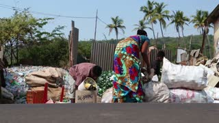 GOA, INDIA - 26 JANUARY 2015: Woman and men sorting waste at a street disposal place in Goa.