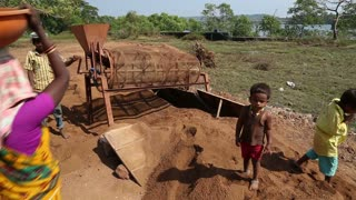 GOA, INDIA - 26 JANUARY 2015: Woman pouring soil in a processing machine, while children play.