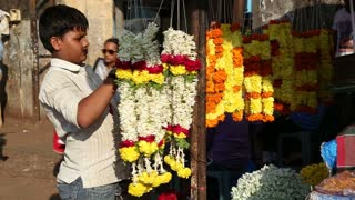 GOA, INDIA - 27 JANUARY 2015: Boy arranging decorations at a street stand in Goa.