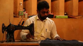 GOA, INDIA - 27 JANUARY 2015: Portrait of Indian man sewing at local market in Goa.