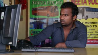 GOA, INDIA - 27 JANUARY 2015: Portrait of Indian man sitting by a counter and working on computer.