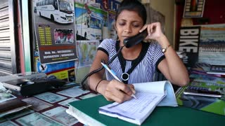 GOA, INDIA - 27 JANUARY 2015: Portrait of Indian woman taking a reservation by the counter.