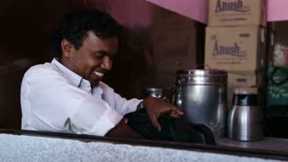 GOA, INDIA - 27 JANUARY 2015: Portrait of smiling Indian man looking inside of a bag.