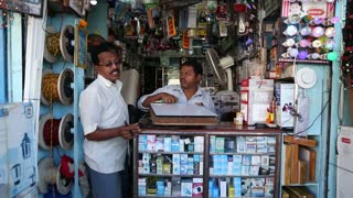 GOA, INDIA - 27 JANUARY 2015: Two Indian man in a small street electronics shop.