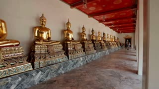 Golden buddha statues aligned in Wat Pho Temple in Bangkok, Thailand.