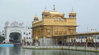 Golden temple in Amritsar, with water in front and crowd standing by entrance.