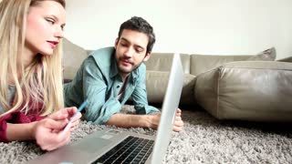 Good looking couple shopping online on laptop
