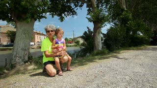 Grand mother and grand daughter looking at geese on the canal du midi in France